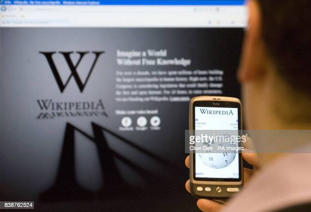 An office worker is greeted by a blacked out Wikipedia page as they attempt to access the site whilst also checking the website on their mobile phone