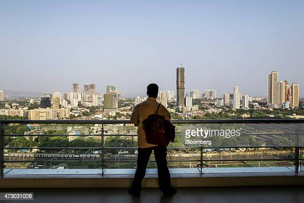 An office worker looks out at commercial and residential towers under construction in Mumbai India on Monday May 11 2015 Mumbai's longcherished dream...