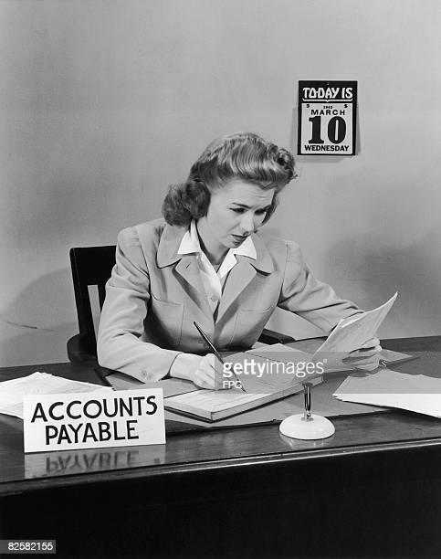 An office worker makes an entry in a ledger circa 1945
