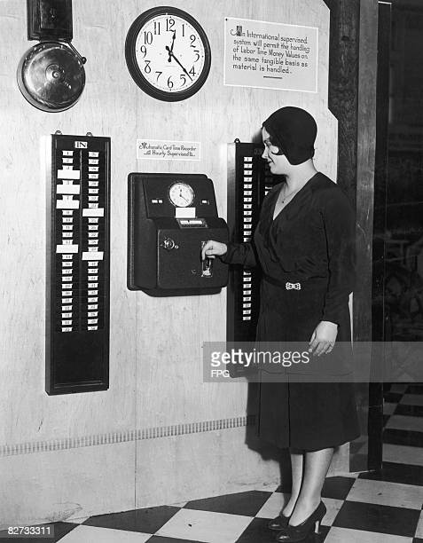 An office worker punches her time card upon arrival at the office circa 1930