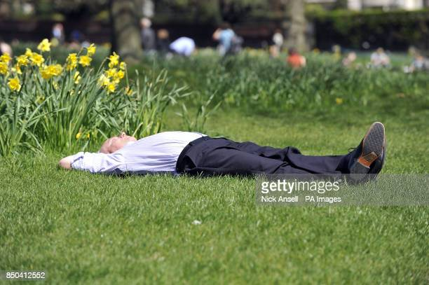An office worker relaxes in the warm spring weather in Green Park central London