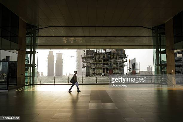 An office worker walks through a building in front of an Indiabulls Real Estate Ltd commercial building construction site in the Lower Parel area of...