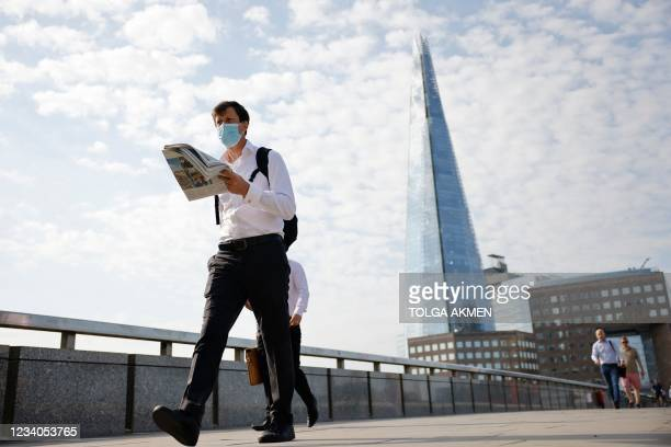 An office worker wearing a facemask crosses London Bridge in London on July 19, 2021. - Virtually all pandemic restrictions were lifted in England...