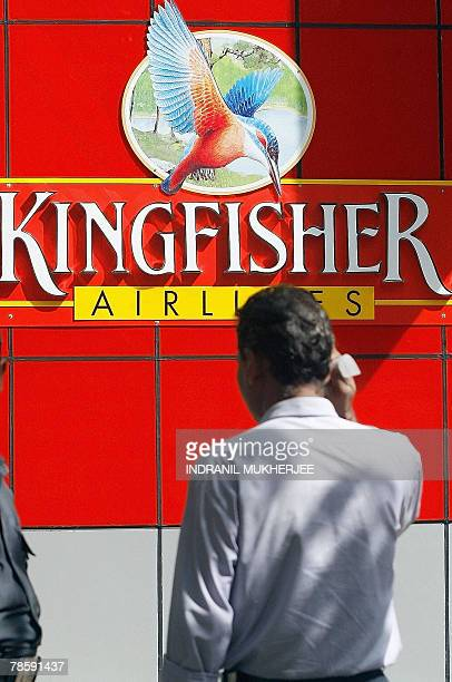 An officegoer walks past the city office of Kingfisher Airlines in Mumbai 20 December 2007 India's biggest discount carrier Deccan will merge with...