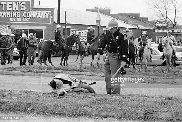 An officer accosts an unconscious woman as mounted police officers attack civil rights marchers in Selma Alabama who were attempting to begin a 50...
