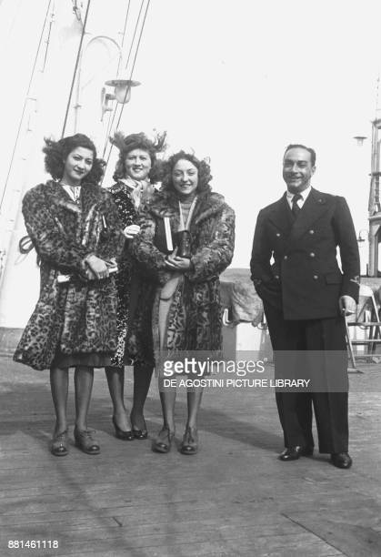 An officer and three young women wearing furs on the deck of the Italian ship the Duilio March 26 Italy 20th century