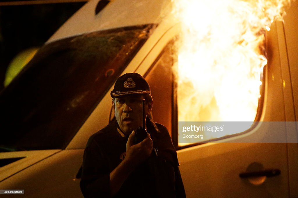 An officer attends to a burning television van during police clashes with protesters on Syntagma Square in central Athens, Greece, on Wednesday, July 15, 2015. Greek police clashed with protesters in central Athens as lawmakers debated a new bailout of up to 86 billion euros ($94 billion) that will impose further austerity on a country already ravaged by recession. Photographer: Matthew Lloyd/Bloomberg via Getty Images
