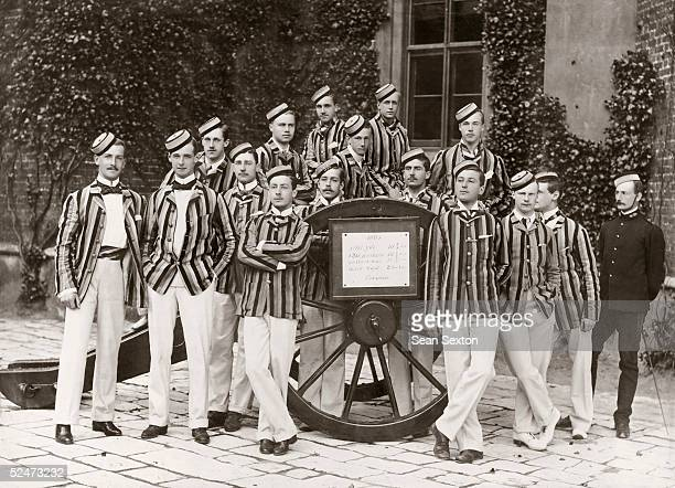 An officer cadets' athletic team at the Royal Military Academy Woolwich London pose by a gun carriage with a board detailing their sporting records...