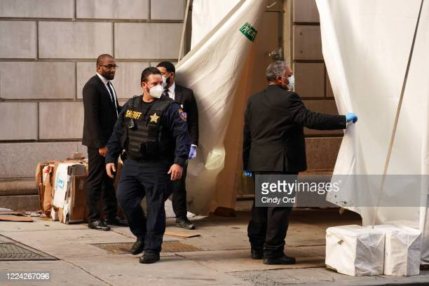 An officer exits the makeshift morgue at Lenox Hill Hospital before escorting the body of Glen Ridge New Jersey police officer Charles Roberts on May...