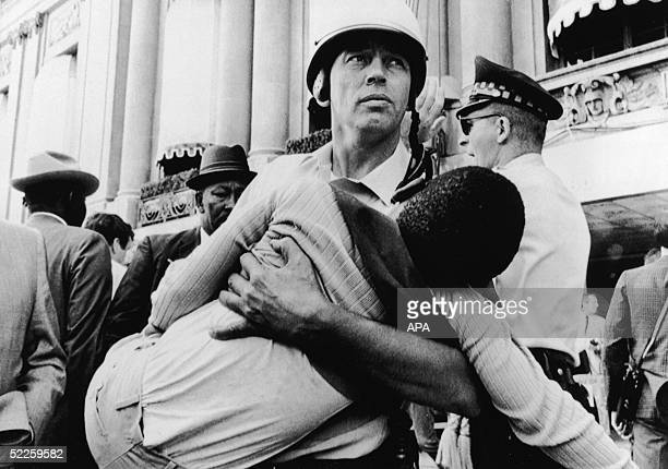 An officer from the Chicago Police Department carries a young antiwar demonstrator a boy who looks to be around 10yearsold after he fainted in the...