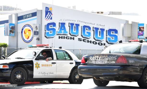 An officer from the Los Angeles Sheriff's Department sits in a vehicle in front of Saugus High School on November 15 2019 in Santa Clarita California...