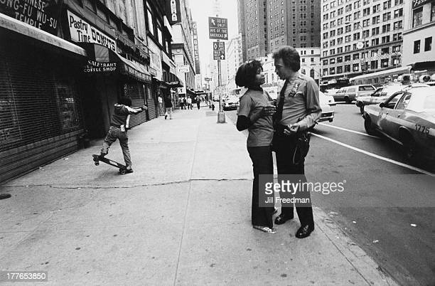 An officer from the Midtown South Precinct talks to a woman on 32nd Street New York City circa 1980