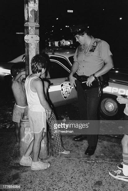 An officer from the ninth precinct talks to local children in the Lower East Side New York City circa 1976