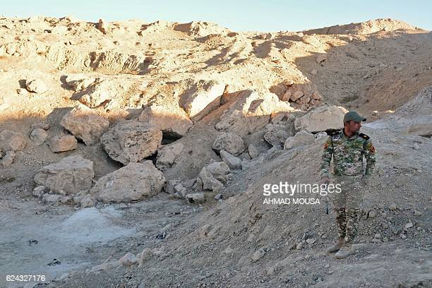 An officer from the Rapid Response Division stands at the site of a suspected mass grave containing the remains of victims of the Islamic State group...