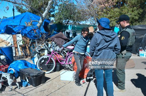 An officer from the Sheriff's Department and a social worker speak with a woman at the homeless encampment beside the Santa Ana River in Anaheim...
