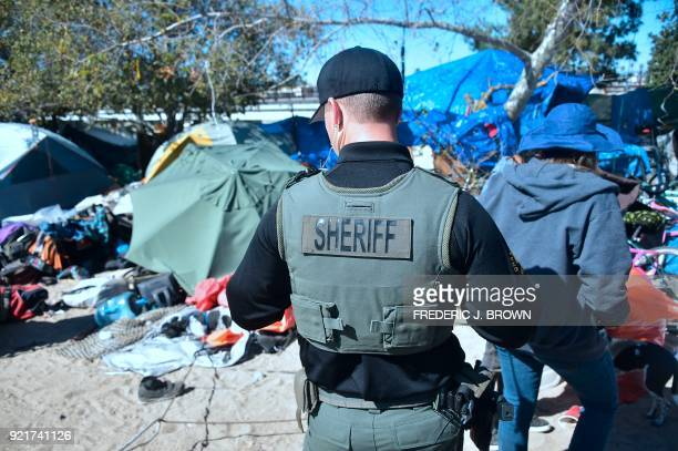 An officer from the Sheriff's Department and a social worker walk the area at the homeless encampment beside the Santa Ana River in Anaheim...