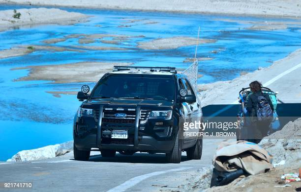 An officer from the Sheriff's Department speaks with a homless woman pulling her cart of belongings beside the Santa Ana River in Anaheim California...