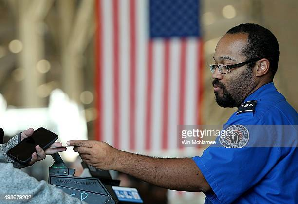 An officer from the Transportation Security Administration checks travel documents for passengers traveling through Reagan National Airport November...