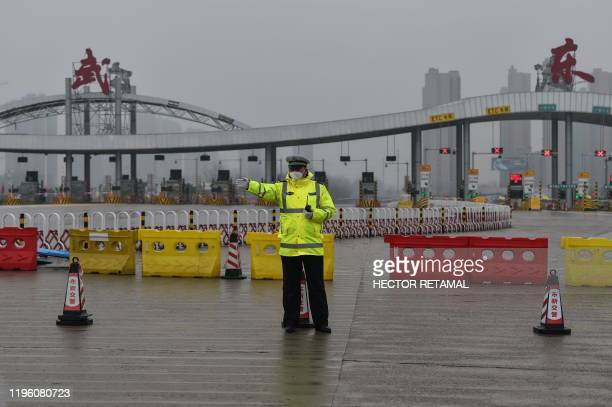 An officer gestures in front of one of the roads blocked by the police to restrict people leaving Wuhan in China's central Hubei province on January...