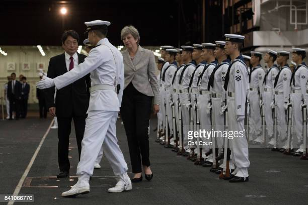 An officer gestures to Britain's Prime Minister Theresa May and Japan's Defence Minister Itsunori Onodera on board the Japanese navy's helicopter...