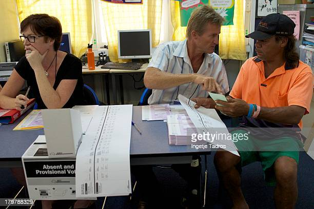 An officer helps a voter at Broome Primary School Members of the public vote at Broome Primary School on September 7 2013 in Broome Australia...