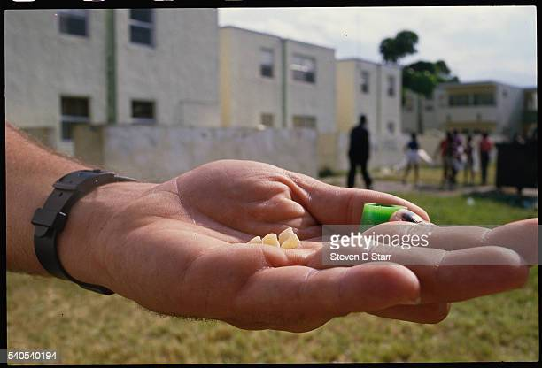 An officer holds some of the drugs confiscated during a drug raid in Miami