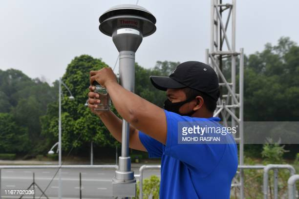 An officer inspects an air pollution analyser at the Air Quality monitoring station in Putrajaya on September 13 2019 Indonesia's forest fires are an...
