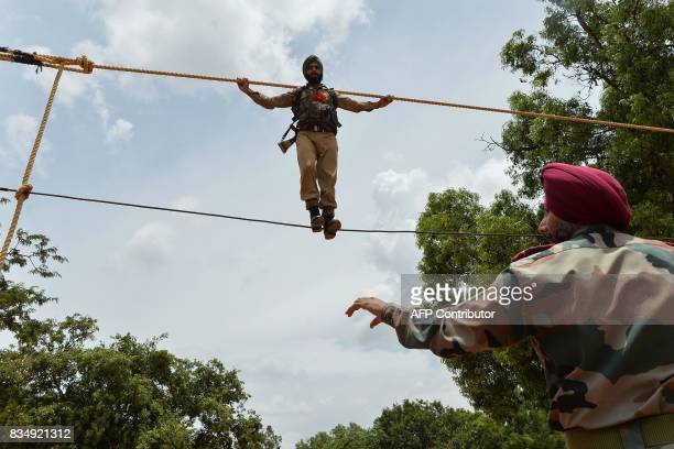 An officer keeps a watch as Indian trainee recruits undergo physical endurance training at the Parachute Regiment Training Centre in Bangalore on...