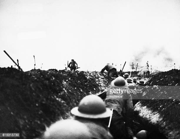 An officer leads the way amidst bursting German shells during the Arras and Cambrai offensive April 7 1918