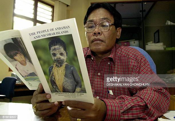 An officer of Anthropoligical Servey of India Anstice Justin looks at a booklet describing life in the Andaman and Nicobar Islands in his office at...