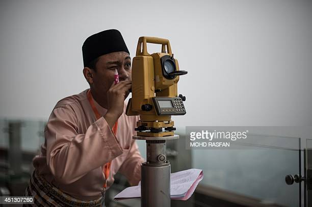 An officer of Malaysia's Islamic authority uses a Theodolite to perform 'rukyah' the sighting of the new moon of Ramadan on the observation deck of...