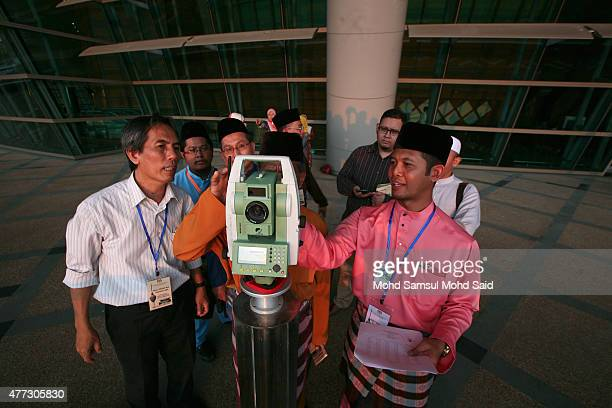 An officer of Malaysia's Islamic authority uses a theodolite to perform 'rukyah' the sighting of the new moon of Ramadan on June 16 2015 in Putrajaya...