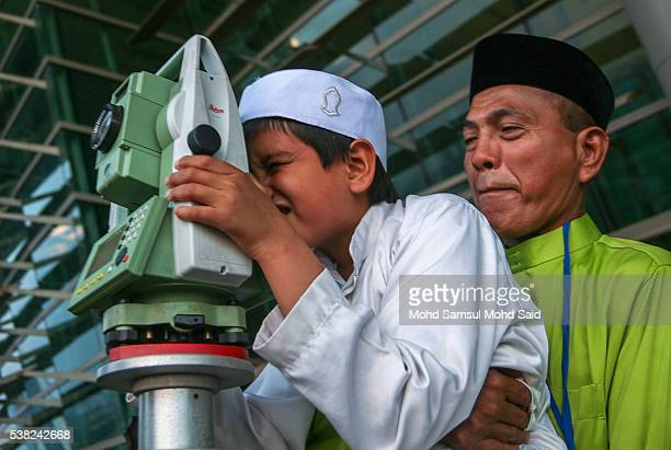 An officer of Malaysia's Islamic authority with children uses a telescope to perform 'rukyah' the sighting of the new moon of Ramadan in Putrajaya...