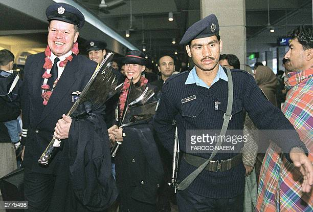 An officer of Pakistan's Airport Security Force personnel guides a British Airways cabin crew through the arrivals hall at Islamabad International...