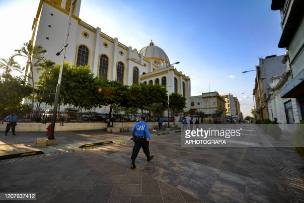 An officer of San Salvador's municipal police walks through an empty street in front of the San Salvador Cathedral on March 18 2020 in San Salvador...