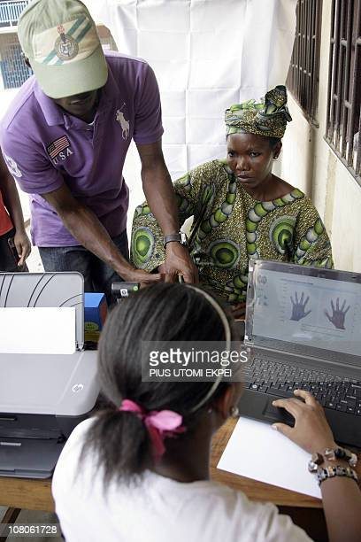 An officer of the Independent Electoral Commission helps a women to do a thumb print check during voter's registration in Lagos on January 15 2011...