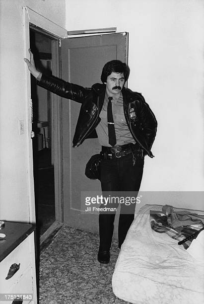 An officer of the NYPD 9th Precinct checks out an apartment in Alphabet City Lower East Side New York City 1978