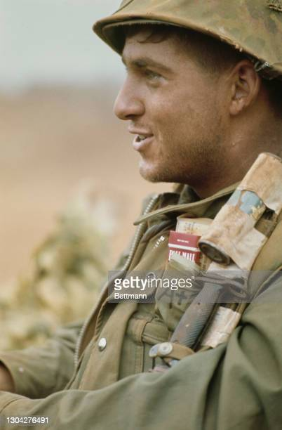 An officer of the United States Marines Corps, a packet of Pall Mall cigarettes in his top pocket, on which is written 'A+', as reinforcements arrive...