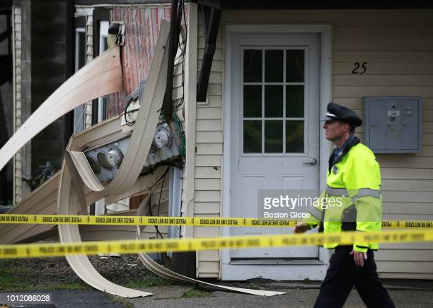 An officer passes a home damaged by a tornado on Chase Avenue in Webster MA on Aug 4 2018 A tornado along with intense rain hit Central Massachusetts...