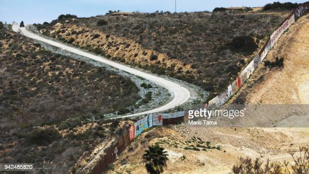 An officer patrols along the border fence at the USMexico border on April 5 2018 in Tijuana Mexico President Trump has issued a decree for the...