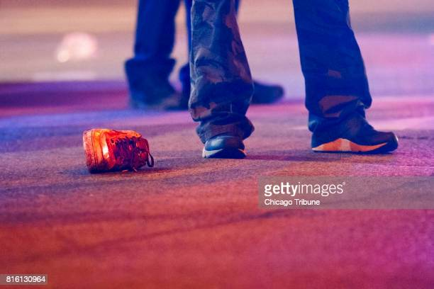 An officer stands next to a bloody shoe at the scene where two people were shot one fatally on the 3900 block of west Arthington Street Sunday July...