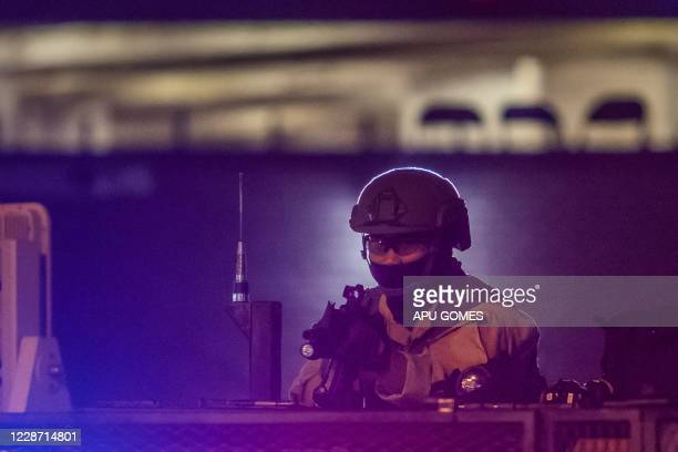 An officer takes position in front of the Los Angeles County Sheriff West Hollywood Station as people protest over the lack of criminal charges in...