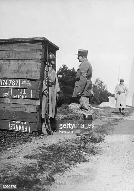 An officer talking to a French soldier in an old railway observation box which has been turned into a sentry box