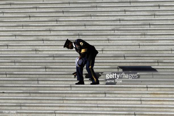An officer walks down the Senate Steps of the Capitol Building picking up military covers that blew off in the fierce wind after the body of former S...
