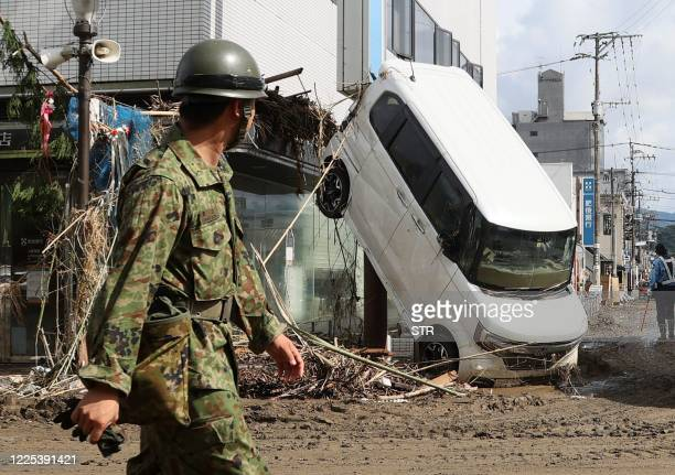 An officer walks psat a damaged car in Hitoyoshi, in Kumamoto Prefecture on July 8, 2020. - Japan will deploy more troops to search for survivors of...