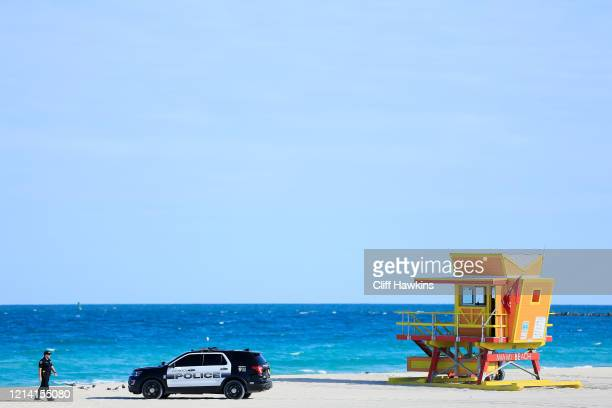 An officer walks toward a police SUV next to the third street lifeguard stand on March 22, 2020 in Miami Beach, Florida. The city of Miami Beach has...