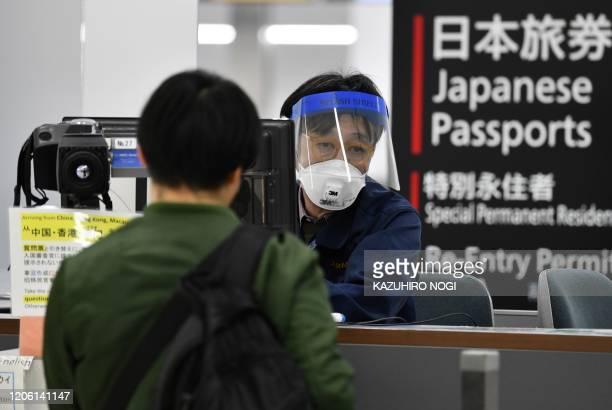 An officer wearing a face mask and shield checks a passenger arriving from Hong Kong, at a quarantine station at Narita airport, Chiba prefecture on...