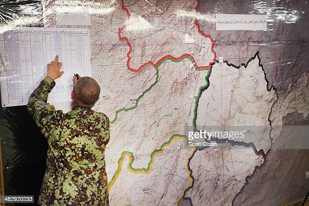 An officer with the Afghan National Army helps to direct security for the election from the tactical operations center at Camp Maiwand on April 5...