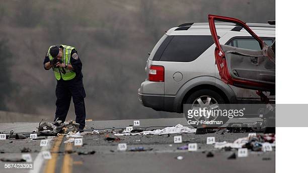 An officer with the California Highway patrol photographs evidence at the wreckage of a car crash on the westbound Pomona Freeway in Diamond Bar on...