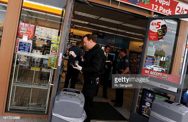 An officer with the Colorado Spring's Crime Scene Unit dust for fingerprints at a Circle K store Friday January 20 at Commerce Center Drive and...